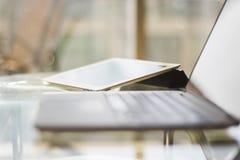 Computer portatile e compressa digitale su una tavola di vetro, profondità bassa di fie Immagine Stock Libera da Diritti