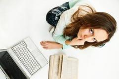 Computer portatile e libro della ragazza Immagini Stock