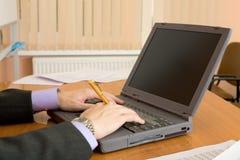 Computer portatile e mani con una penna Fotografia Stock Libera da Diritti