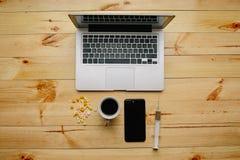 Computer portatile e smartphone con le medicine e caffè su una tavola di legno fotografia stock