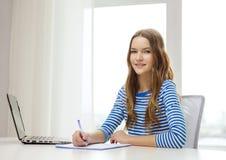 Computer portatile e taccuino sorridenti dell'adolescente Immagine Stock Libera da Diritti