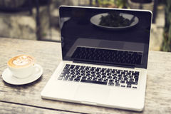 Computer portatile e tazza di cappuccino su una tavola di legno Immagine Stock