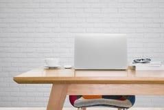 Computer portatile e una tazza di caffè sulla tavola di funzionamento in studio fotografie stock