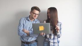 Computer portatile felice della tenuta delle coppie della miscela-corsa mentre stando e celebrando isolato sopra il fondo grigio  archivi video