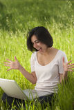 Computer portatile funzionante della donna ispanica Immagini Stock Libere da Diritti