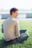 Computer portatile funzionante di spirito del giovane sul prato inglese verde Immagine Stock Libera da Diritti
