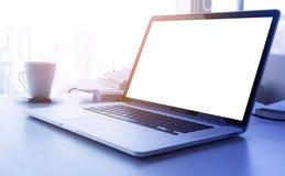 Computer portatile giallo-chiaro di effetto del filtro con lo schermo in bianco sull'ufficio della tavola dello scrittorio immagine stock