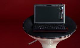 Computer portatile moderno su una presidenza con i vetri Immagini Stock Libere da Diritti