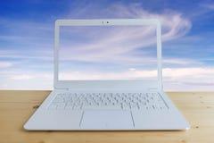 Computer portatile moderno sullo scrittorio di legno con il fondo del cielo blu Fotografia Stock Libera da Diritti