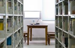 Computer portatile nella libreria Immagini Stock