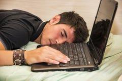 Computer portatile seguente di sonno stanco del giovane Immagine Stock
