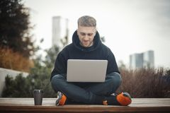 Computer portatile sorridente della tenuta del giovane sulle ginocchia Immagini Stock Libere da Diritti