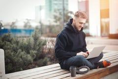 Computer portatile sorridente della tenuta del giovane sulle ginocchia La tazza di caffè nero è accanto lui Immagini Stock