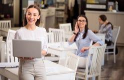 Computer portatile sorridente piacevole della tenuta della donna immagine stock libera da diritti