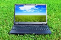 Computer portatile su erba Fotografie Stock