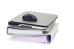 Computer portatile su una pila di dispositivi di piegatura di archivio. Fotografie Stock