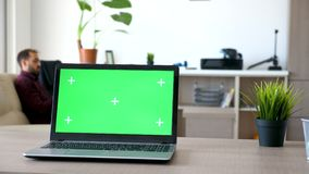 Computer portatile su uno scrittorio nel salone con uno schermo verde isolato e segni per seguire stock footage