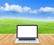 Computer portatile sul pavimento di legno con i campi ed il cielo blu verdi b Fotografia Stock