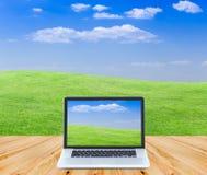 Computer portatile sul pavimento di legno con i campi ed il cielo blu verdi b Fotografie Stock