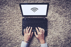 Computer portatile sul pavimento Mani della donna che scrivono sulla tastiera fotografie stock
