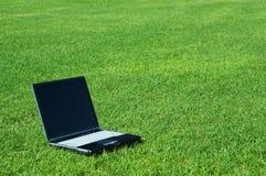 Computer portatile sull'erba Fotografia Stock