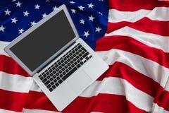 Computer portatile sulla bandiera americana con il tema del 4 luglio Fotografia Stock