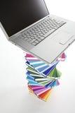 Computer portatile sulla pila di libro a spirale, vista superiore Immagini Stock