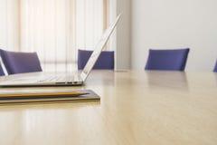 Computer portatile sulla Tabella con la sala del consiglio di riunione dell'ufficio di affari dei sedili fotografie stock libere da diritti