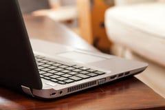 Computer portatile sulla tavola di legno nella casa Fotografie Stock Libere da Diritti