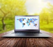 Computer portatile sulla tavola di legno sulla natura Immagini Stock Libere da Diritti