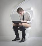 Computer portatile sulla toilette Immagine Stock