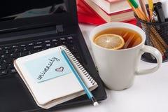 Computer portatile sullo scrittorio del ` s dello studente, sul monitor un autoadesivo con l'università di parola immagini stock libere da diritti