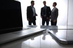 Computer portatile sullo scrittorio, tre persone di affari Fotografia Stock
