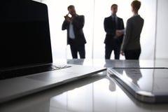 Computer portatile sullo scrittorio, tre persone di affari Immagini Stock Libere da Diritti