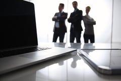 Computer portatile sullo scrittorio, tre persone di affari Fotografie Stock Libere da Diritti