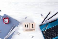 Computer portatile, sveglia rossa e rifornimenti, calendario di legno con data il 1° settembre sullo scrittorio bianco Di nuovo a fotografia stock