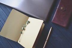 Computer portatile, taccuino con il ramo dell'eucalyptus, penna e portafoglio sulla piattaforma di legno Bello posto di lavoro fotografie stock libere da diritti
