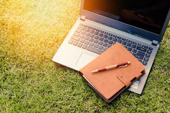 Computer portatile, taccuino, smartphone e penna su erba verde fotografia stock