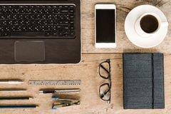 Computer portatile, taccuino, telefono, caffè, vetri, penna e matita sulla scrivania di legno Immagini Stock Libere da Diritti