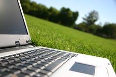 Computer portatile in un campo Immagini Stock Libere da Diritti