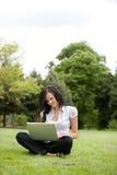Computer portatile usando femminile casuale Immagine Stock