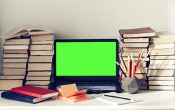 Computer portatile verde dello schermo, pila di libri, taccuini e matite sulla tavola bianca, fondo di concetto dell'ufficio di i immagine stock