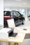 Computer, printer and documents on wooden desk and new car Royalty Free Stock Photography