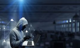 Computer privacy attack. Mixed media. Hacker man in hoodie with laptop in hands. Mixed media Royalty Free Stock Images