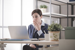 Computer problem. Young businesswoman having problems with her computer, she is staring shocked at the screen with an hand over mouth Royalty Free Stock Photo