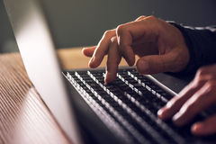 Computer programmer and hacker hands typing laptop keyboard. Close up low key with selective focus stock photo