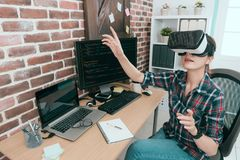 Computer programmer wearing VR technology goggles. Professional young computer programmer wearing VR technology goggles working and using hands touching screen Royalty Free Stock Photo