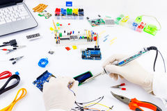 Computer programming microelectronics. Engineer is working wiith pliers and plumb. Microcontrollers, chips, resistors and light-emitting diodes on white desktop royalty free stock images