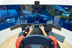 Computer racing simulator. Man plays on a computer racing simulator stock image
