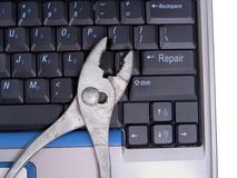 Computer Repair. Pliers on laptop keyboard with Enter key changed to say Repair Royalty Free Stock Images
